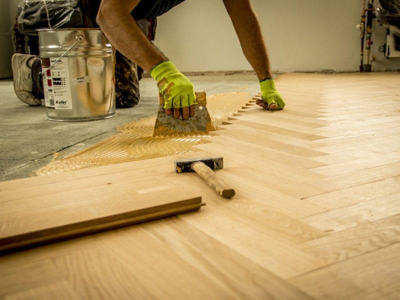 Fotoreportaż, pracownik nakładający klej na podłogę