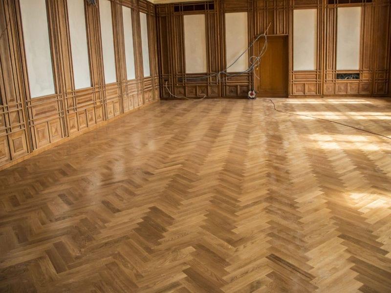 Fotoreportaż, pomieszczenie z drewnianym, polakierowanym parkietem